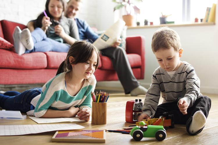 Haus-familie-sofa-kinder-spielen-wohnung-shutterstock 555730207 in Wohneigentum: Vorschläge von CDU, SPD und FDP setzen Fehlanreize