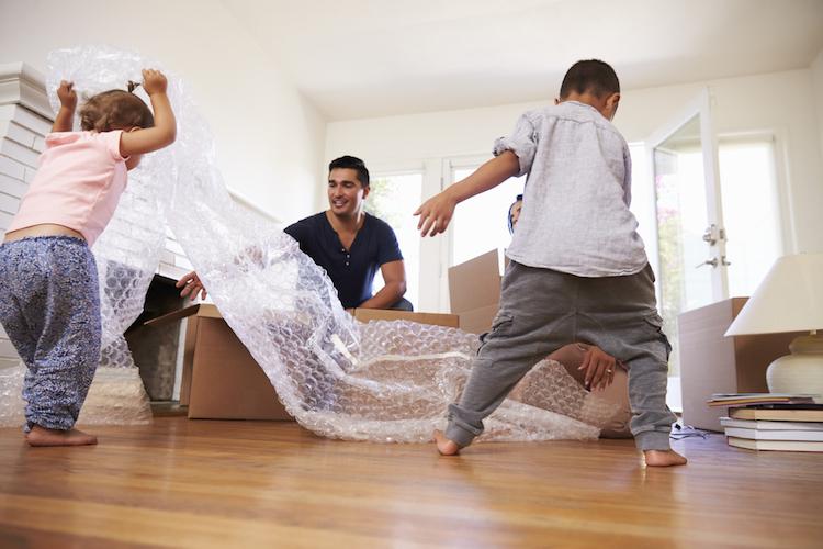 Familie mit zwei Kindern packt Kisten aus und spielt dabei mit Luftpolsterfolie.