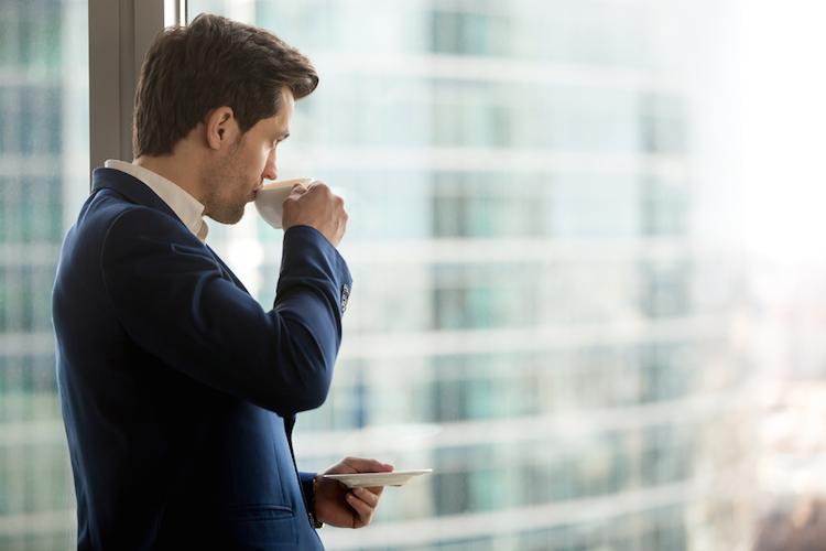 Angestellter-ausblick-buero-kaffee-anzug-investor-shutterstock 658103245 in Für eine Rezession ist es noch zu früh