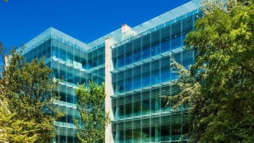 Foto des Gebäudes. Zu sehen sind fünf Stockwerke und viel Glas.