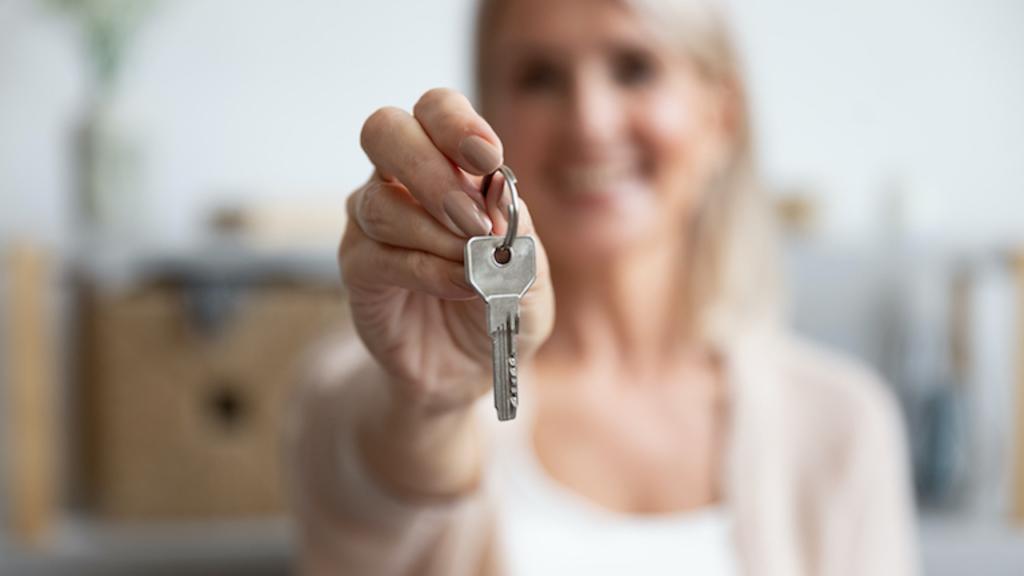 Junge Frau hält Haustürschlüssel in die Höhe und übergibt damit das verkaufte Haud an den Käufer.