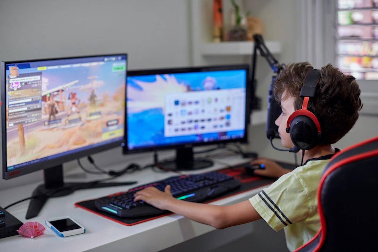 """Teenager sitzt vor mehreren Monitoren und spielt """"Fortnite"""""""