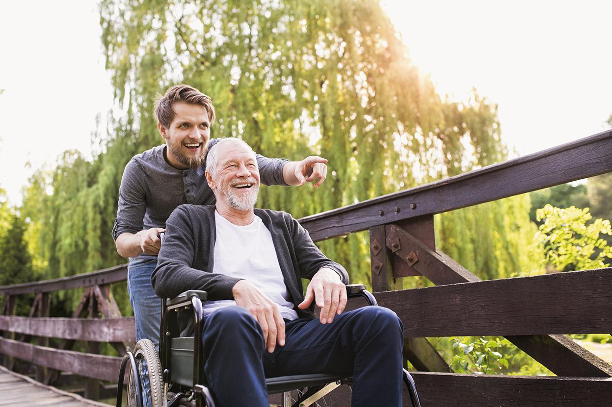 Sohn läuft mit Vater im Rollstuhl