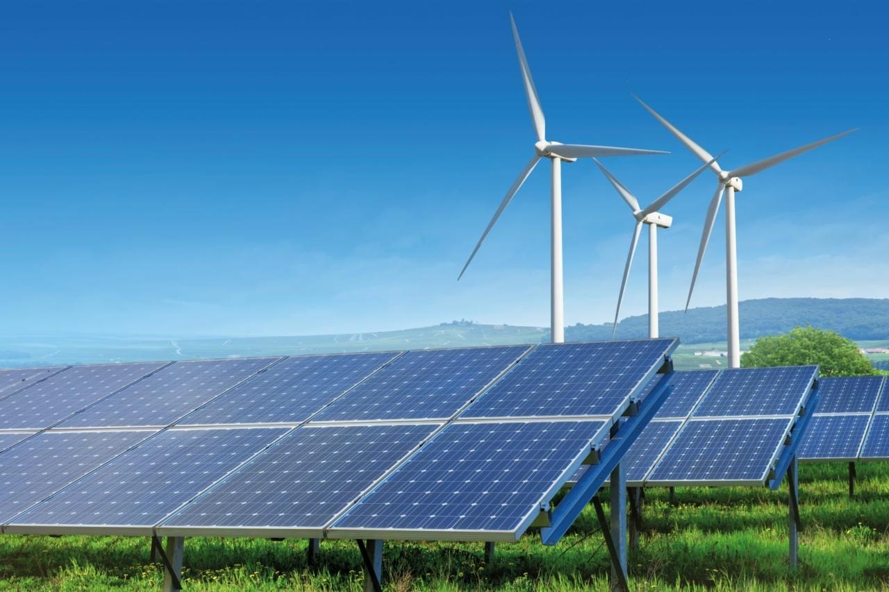 Solaranlage mit Windrädern im Hintergrund