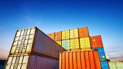 Bunte gestapelte Container vor blauem Himmel
