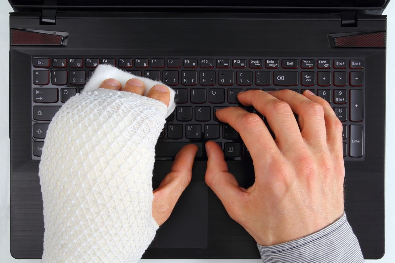 Zwei Hände auf Laptop-Tastatur, eine davon mit Gipsschiene