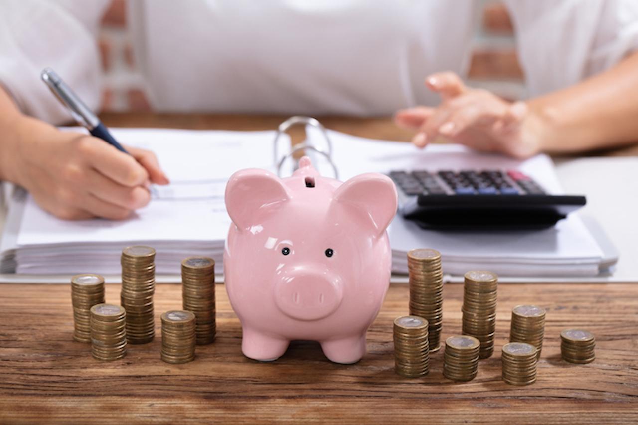 Sparschwein vor gestapelten Geldmünzen