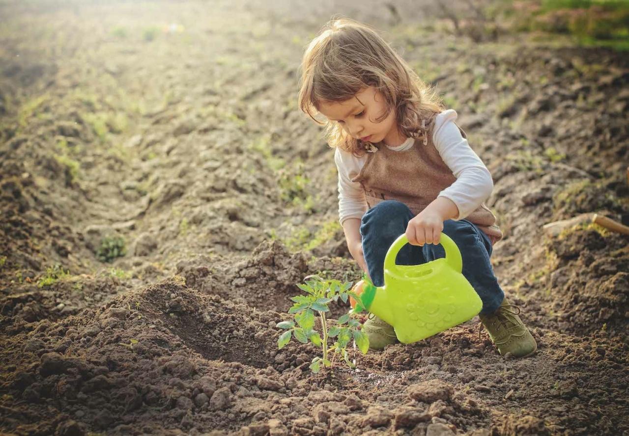 Mädchen spielt mit grüner Gießkanne