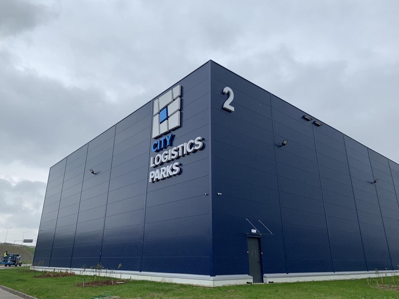 Schwarzes fenststerloses Logistik Gebäuden von AEW