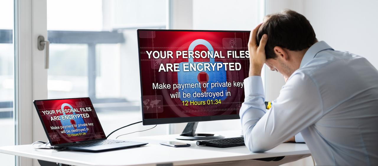 Mann vor zwei Computerbildschirmen, die von Hackern gesperrt wurden.