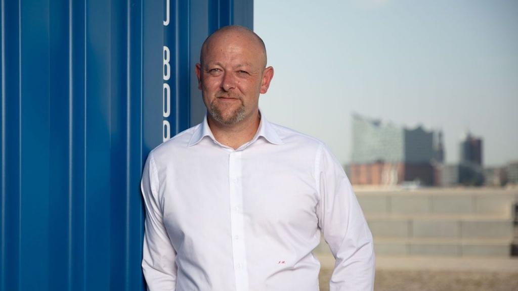 Solvium Geschäftsführer Jürgen Kestler lehnt an einem Container, im Hintergrund die Hamburger Elbphilharmonie