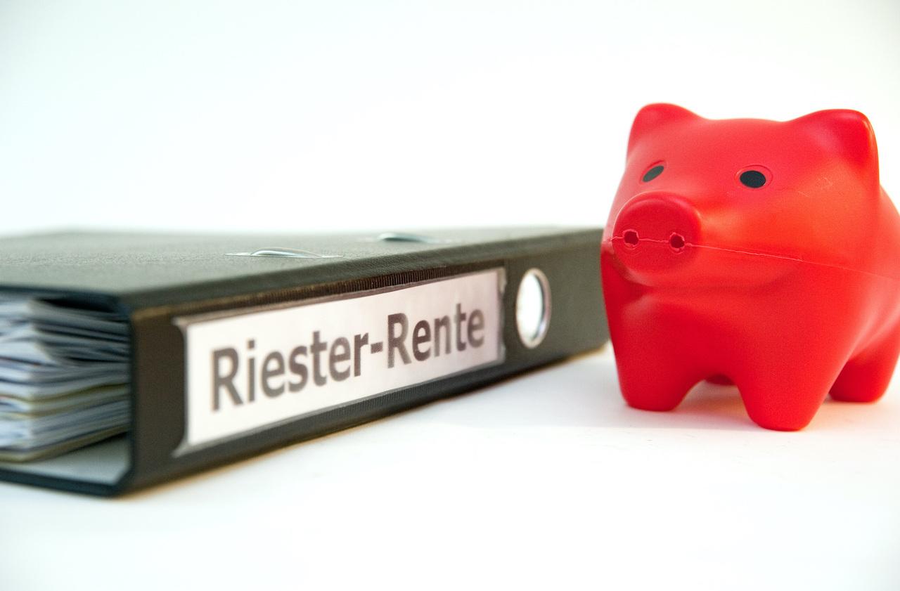 """ILLUSTRATION - Ein Sparschwein steht am 19.01.2012 in Berlin neben einem Ordner mit der Aufschrift """"Riester-Rente""""."""