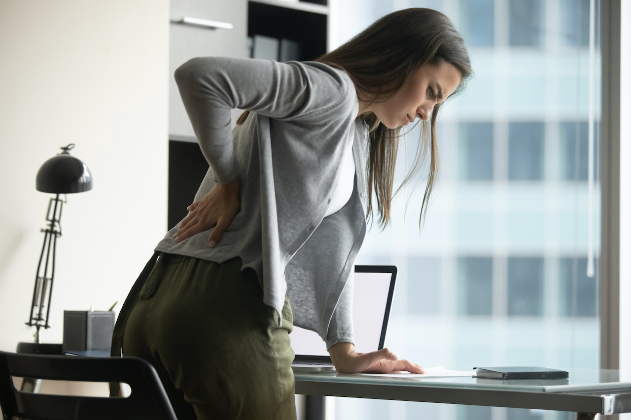 Junge FRau, dei vom Schreibtisch mit Rückenschmerzen aufsteht