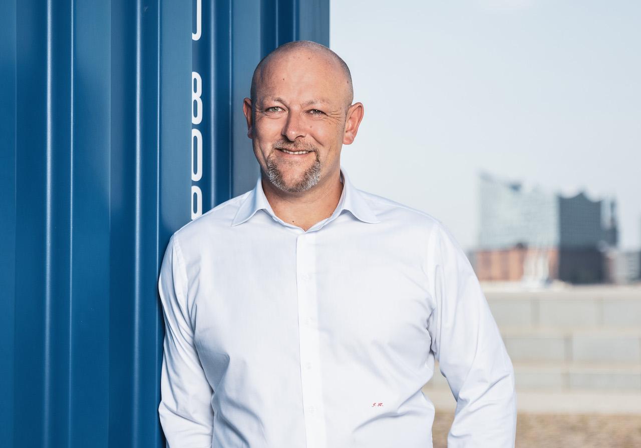 Solvium Geschäftsführer Jürgen Kestler lehnt an einem blauen Container