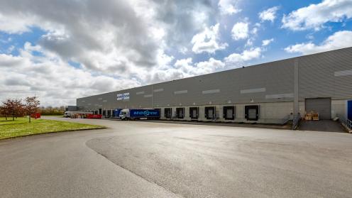 LKW stehen an dem riesigen Logistikgebäude, das REInvest verkauft hat.