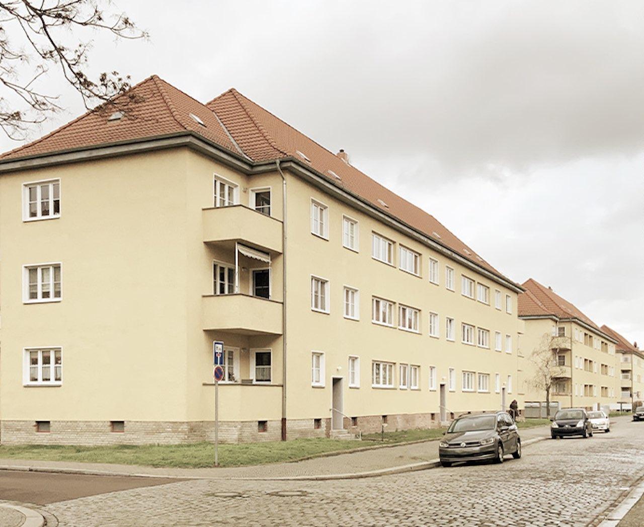 Von AS Unternehmensgruppe erworben: Gelbe Mehrfamilienhäuser mit rotem Dach.