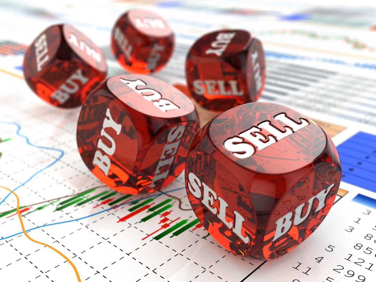 """Würfel mit dem Aufdruck """"Buy"""" und """"Sell"""" auf einem Kursverlauf"""