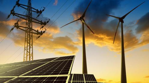 Windräder, Solaranlagen und Strommast in der Dämmerung als Symbolbild für Klimavest Commerz Real