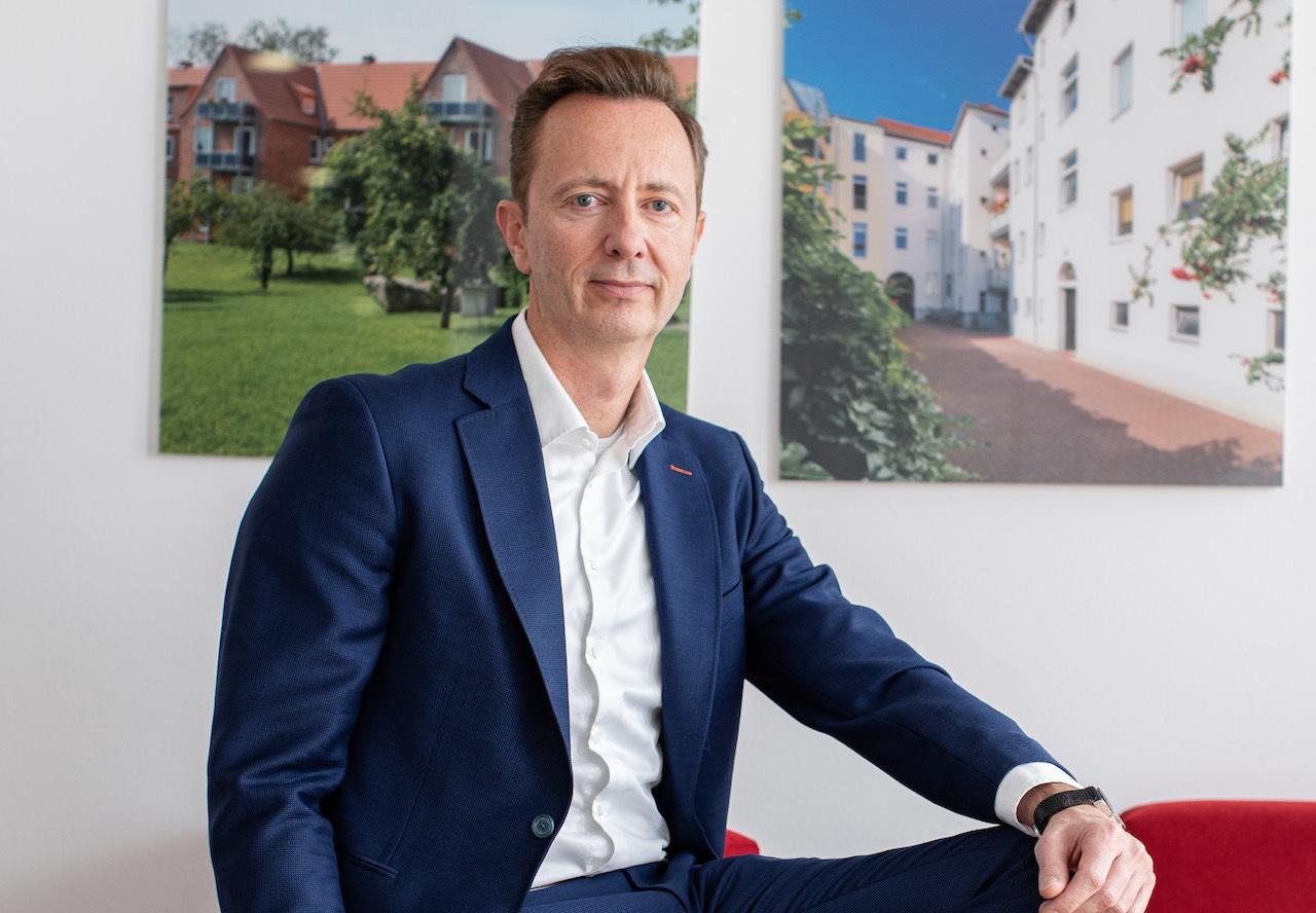 Primus Valor Vorstand Gordon Grundler vor zwei Objektfotos