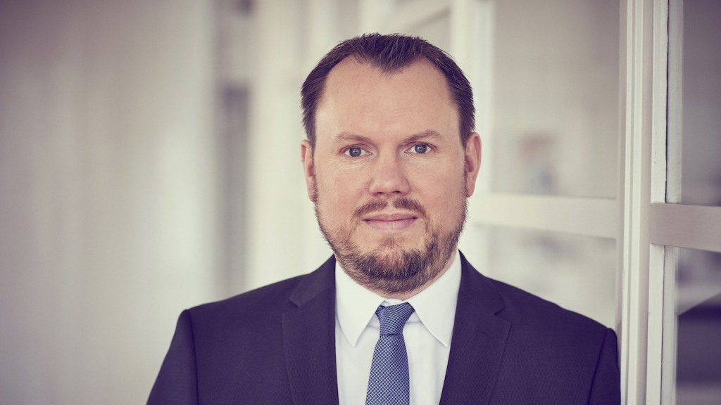 Jan-Peter Schmidt, Vorstand der Deutschen Zweitmarkt AG, vor einem gläsernen Büro