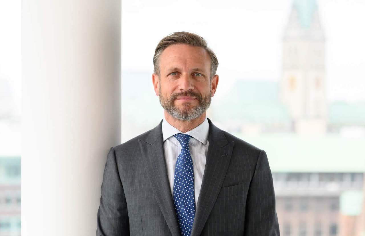 CEE Chef Detlef Schreiber vor dem verschwommenen Hintergrund des Hamburger Rathauses