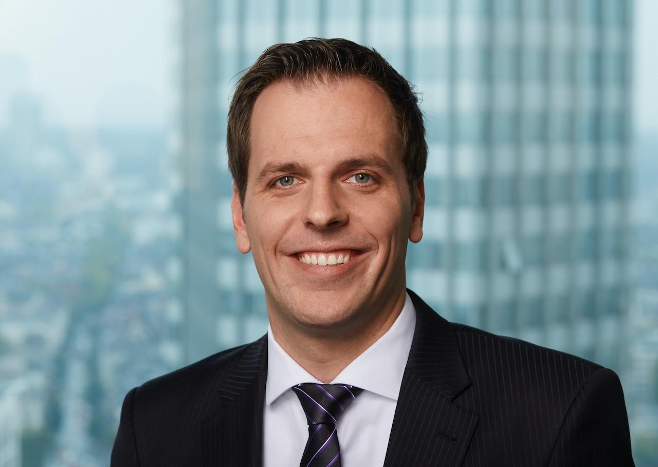 Schroders KVG-Geschäftsführer Nils Heetmeyer vor dem Hintergrund einer Hochhaus-Silhouette