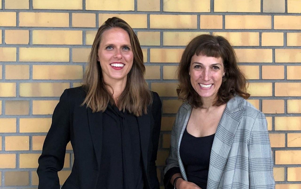 Sophie Kazmierczak und Tanja Volksheimer von der Bundesinitiative Impact Investing vor einer gelben Backstein-Wand..