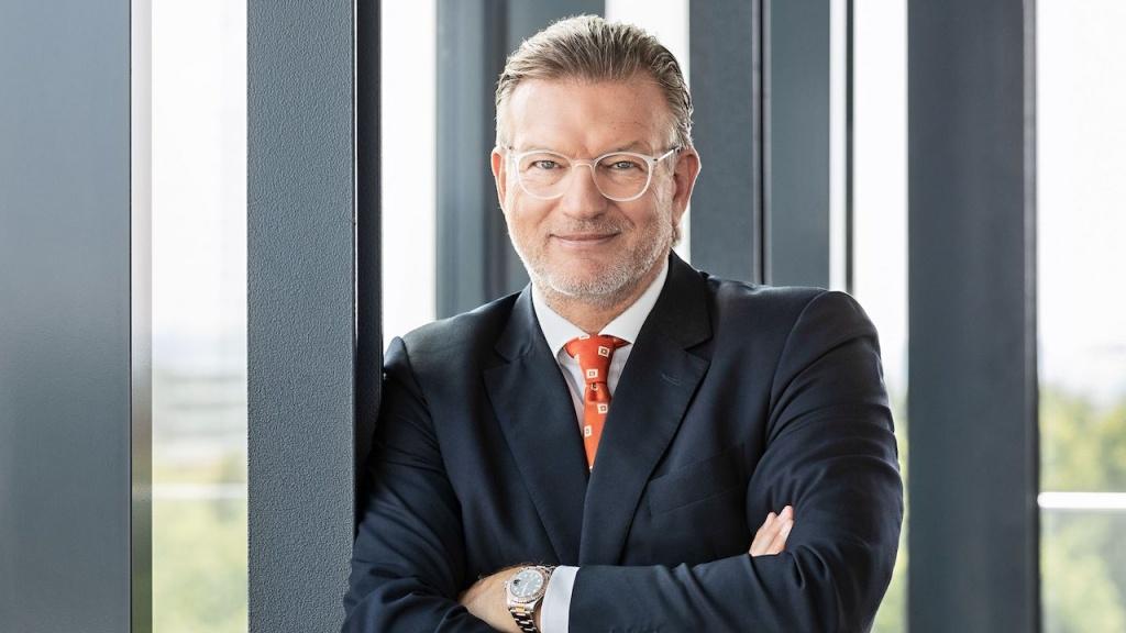 Paribus Chef Thomas Böcher lehnt an einem Pfosten in einem verglasten Büro