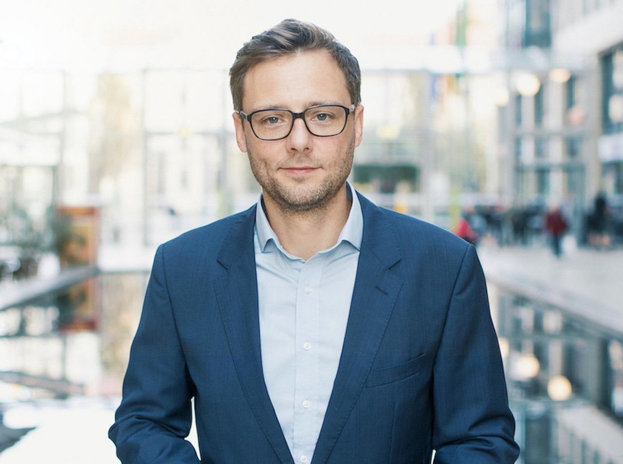 Seedmatch Geschäftsführer Johannes Ranscht vor dem Hintergrund einer Einkaufgspassage