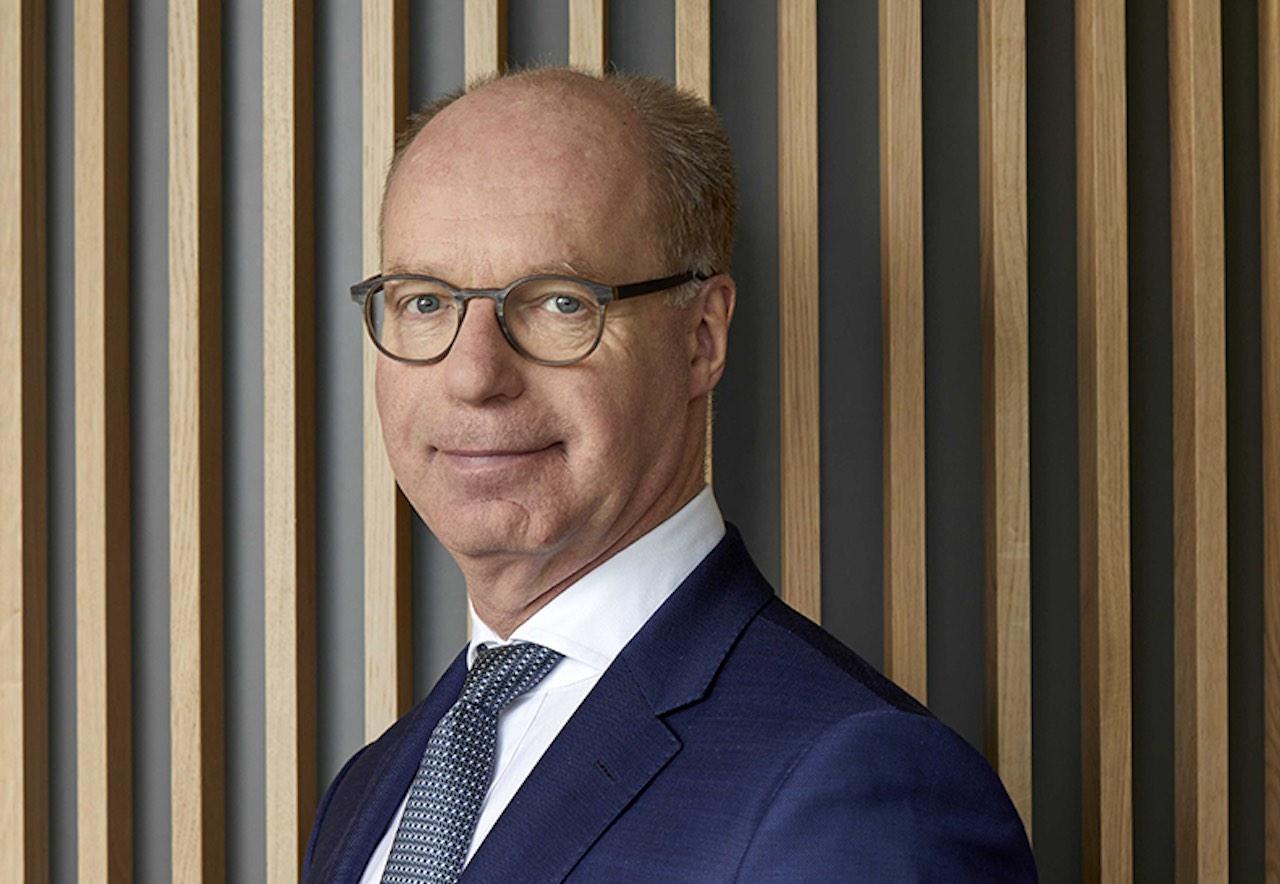 Lloyd Fonds CEO Achim Plate vor einer Wand mit senkrechten Holzleisten