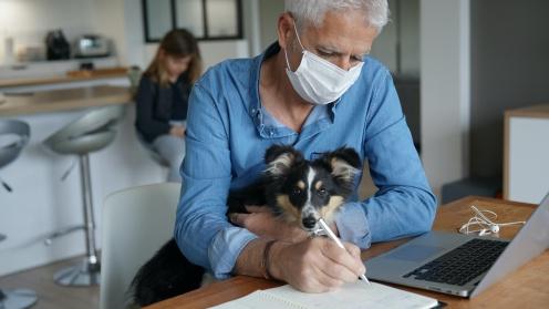 Alster Mann mit Hund auf Schoss arbeitet von zu Hause