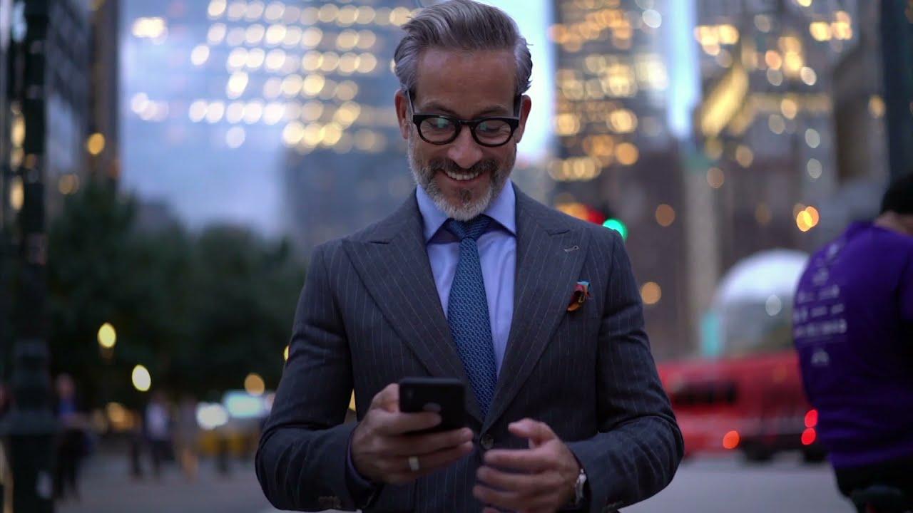 Mann in Anzug schaut lachend auf Handy