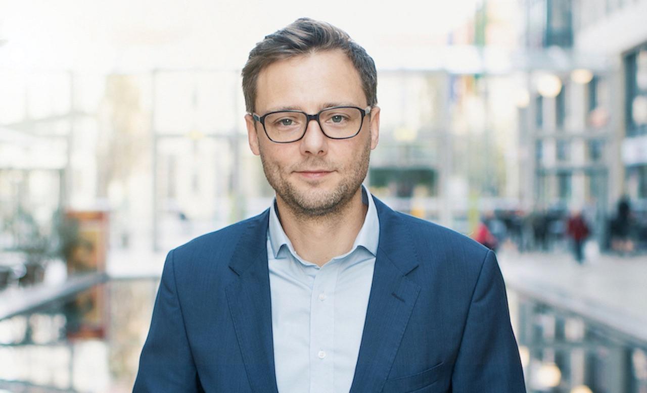 Seedmatch Geschäftsführer Johannes Ranscht vor dem Hintergrund einer Einkaufspassage