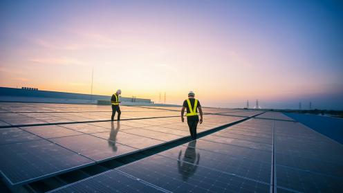 Zwei Arbeiter auf einem Dach mit Solar Anlagen